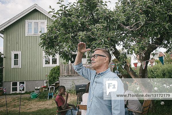 Älterer Mann schirmt Augen ab  wenn er während einer Gartenparty im Garten steht