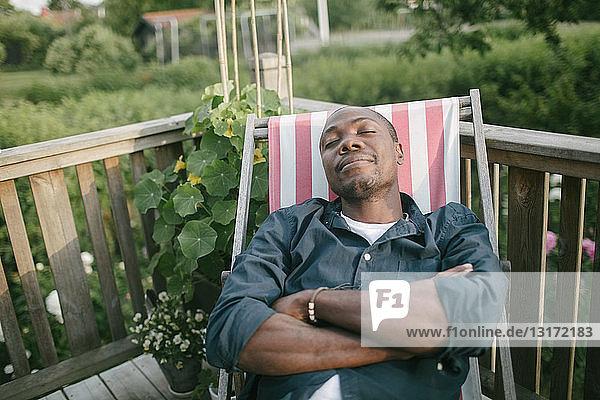 Mittelgroßer erwachsener Mann mit geschlossenen Augen  der sich auf einem Liegestuhl auf der Veranda entspannt