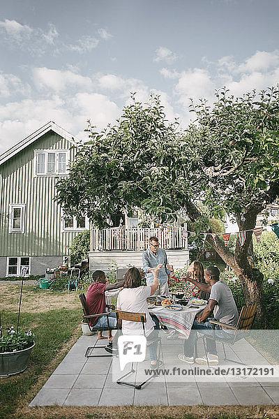 Mehrgenerationen-Familie trinkt während der Gartenparty auf der Terrasse
