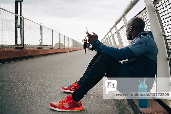 Sportsman holding mobile phone while looking at female athlete running on footbridge
