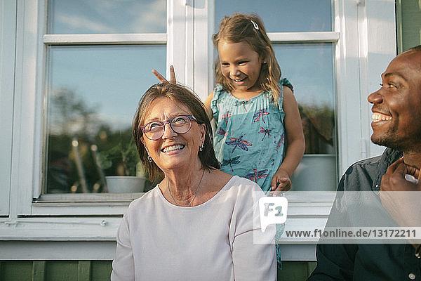 Glückliche Mehrgenerationen-Familie gegen Fenster an der Veranda