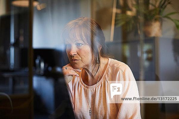 Reife Geschäftsfrau mit Computer durch Glas im Büro gesehen