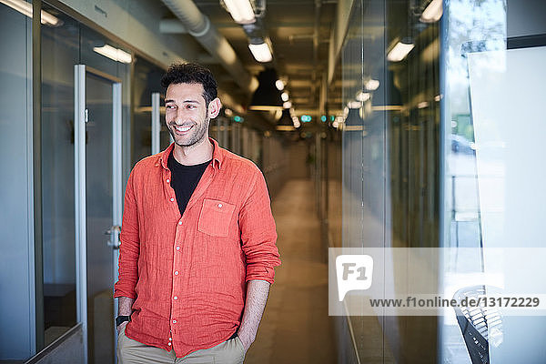 Lächelnder junger Geschäftsmann schaut weg  während er in einem kreativen Büro auf den Flur geht