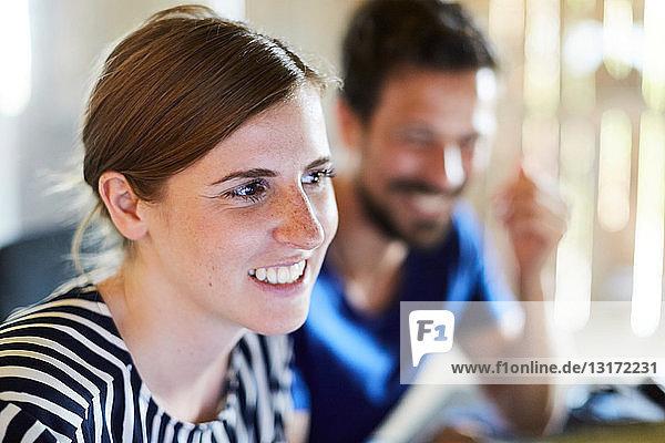 Lächelnde Geschäftsfrau schaut weg  während sie neben einem männlichen Kollegen im Kreativbüro sitzt