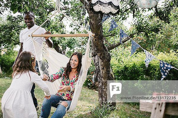 Vater schiebt Hängematte  während eine glückliche Frau die Hand ihrer Tochter im Garten hält