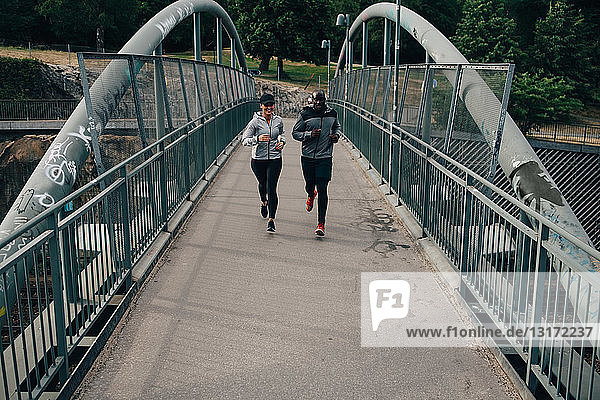 Full length of male and female friends jogging on footbridge in city