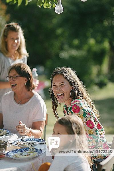 Glückliches Mädchen beim Mittagessen mit Mutter und Großmutter am Tisch während der Gartenparty