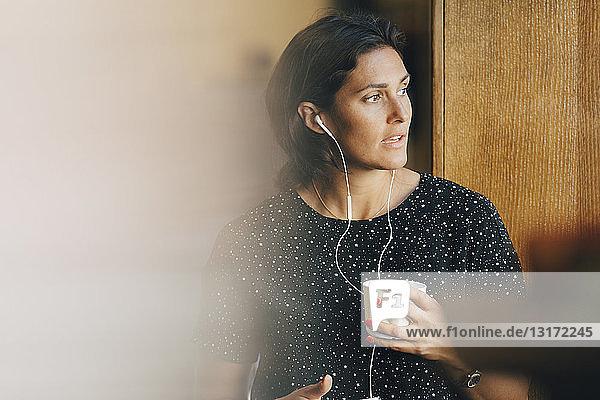 Mittlere erwachsene Geschäftsfrau  die eine Kaffeetasse hält  während sie im Büro über Kopfhörer spricht