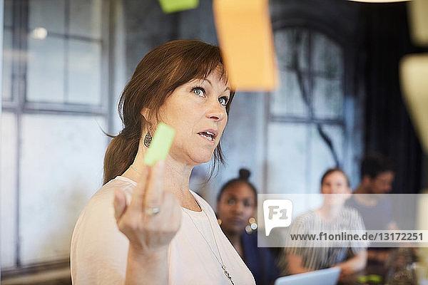 Geschäftsfrau bespricht Ideen mit Kollegen über Haftnotizen im Sitzungssaal