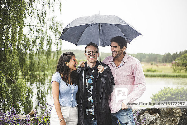 Happy friends standing below umbrella during weekend getaway