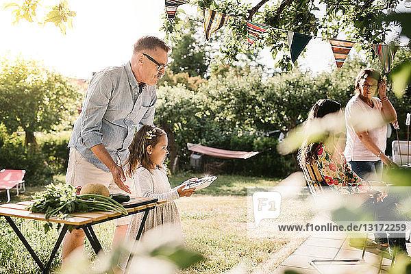 Großvater mit Enkelin  die im Hinterhof Essen auf einem Teller trägt
