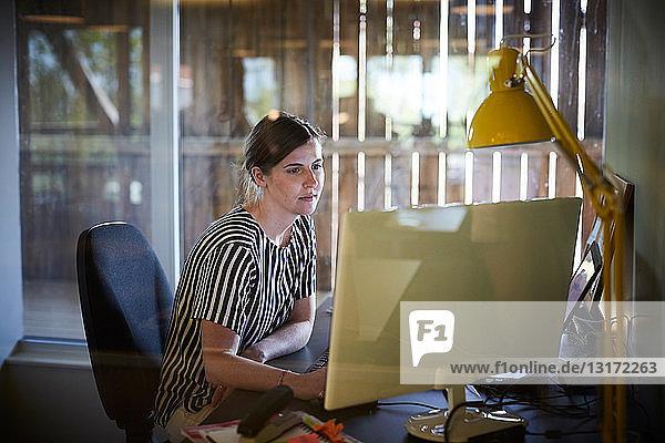 Kreative Geschäftsfrau mit Computer am Schreibtisch im Büro