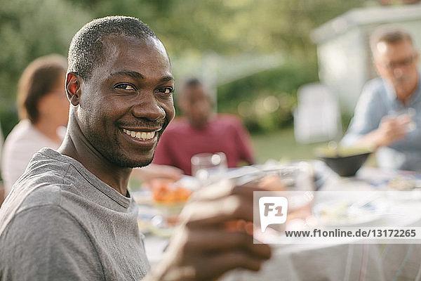 Porträt eines lächelnden mittelgroßen Mannes  der während einer Gartenparty ein Getränk in der Hand hält