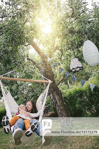 Mutter und Tochter lächeln beim Schaukeln auf der Hängematte im Garten
