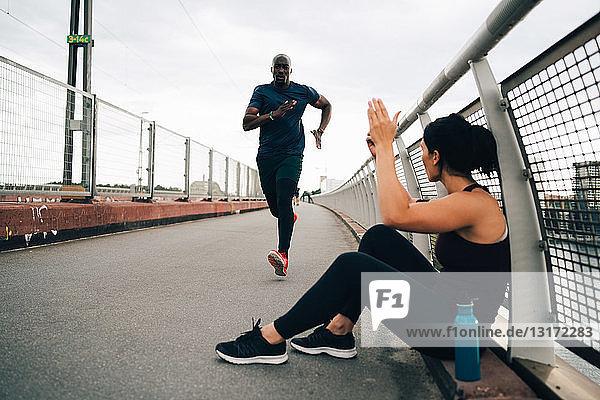 Sportswoman cheering male athlete running on footbridge in city