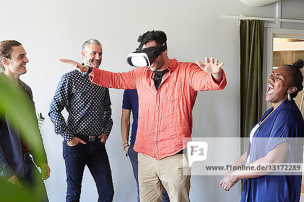 Fröhliche Geschäftsleute betrachten männliche Kollegen  die einen Virtual-Reality-Simulator im Büro benutzen
