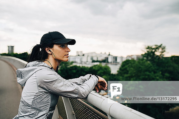 Tired sportswoman looking away while leaning on railing at footbridge in city