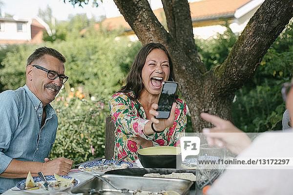 Fröhliche Frau zeigt einer älteren Frau ein Smartphone  während sie während einer Gartenparty am Tisch sitzt