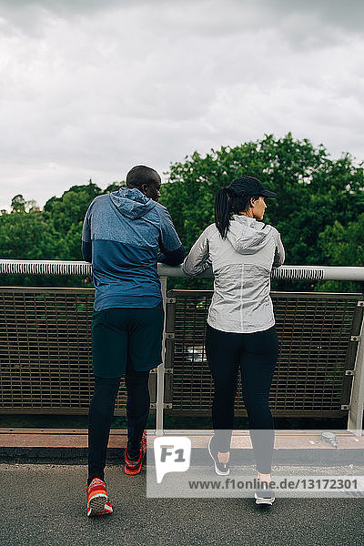Rear view of male and female athletes looking away while standing on footbridge in city