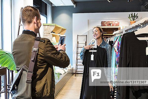 Mann fotografiert Frau mit Smartphone  die ein Kleid in der Boutique hält