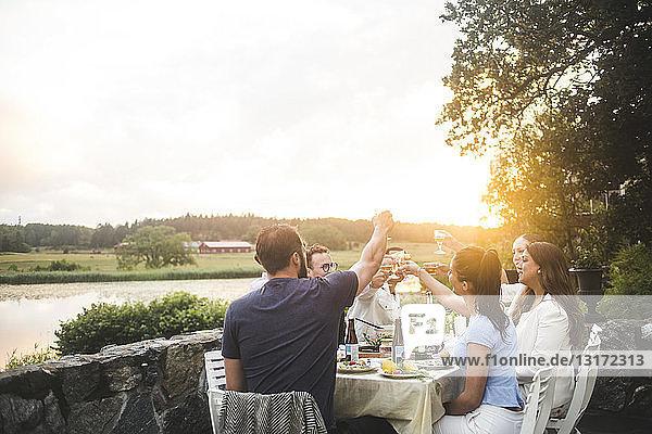 Männliche und weibliche Freunde stoßen bei Sonnenuntergang am Esstisch auf Getränke gegen den Himmel an
