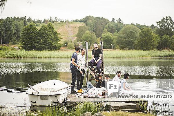 Glückliche Freunde genießen am Wochenende auf dem Steg über dem See