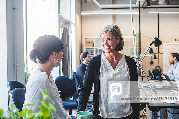 Kolleginnen lächeln beim Gespräch am Schalter im Büro