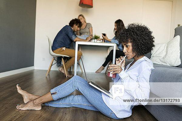 Frau mit Erfrischungsgetränk sitzt auf dem Boden und benutzt einen Laptop mit Freunden im Hintergrund