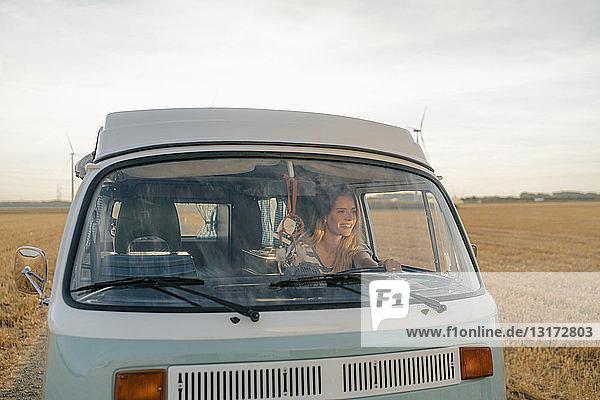 Lächelnde junge Frau fährt Wohnmobil in ländlicher Landschaft