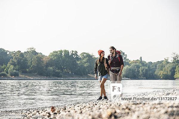 Lächelndes junges Paar mit Rucksäcken beim Spaziergang am Flussufer
