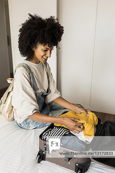 Smiling woman sitting on bed with suitcase