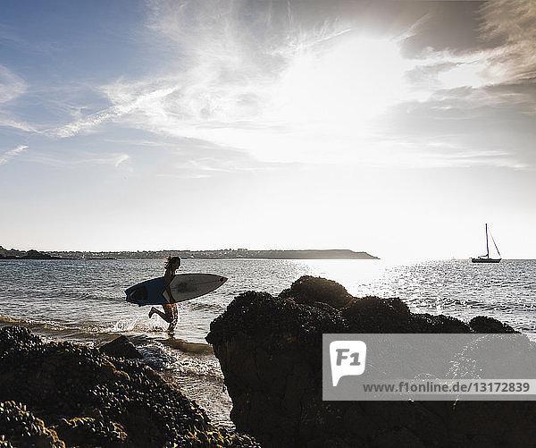 Frankreich,  Bretagne,  junge Frau mit Surfbrett im Meer