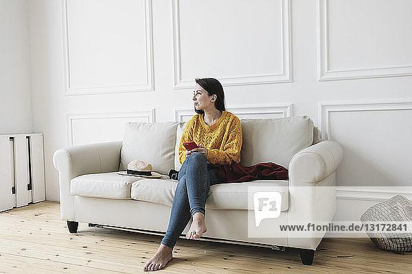 Entspannte junge Frau mit Smartphone sitzt im neuen Zuhause auf der Couch und schaut in die Ferne