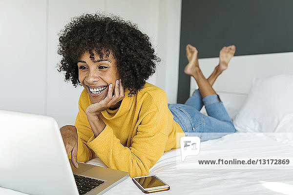Happy woman lying on bed using laptop