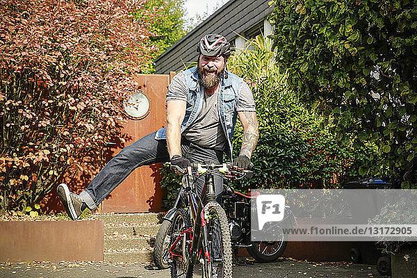 Porträt eines glücklichen Mannes beim Wechsel vom Motorrad aufs Fahrrad