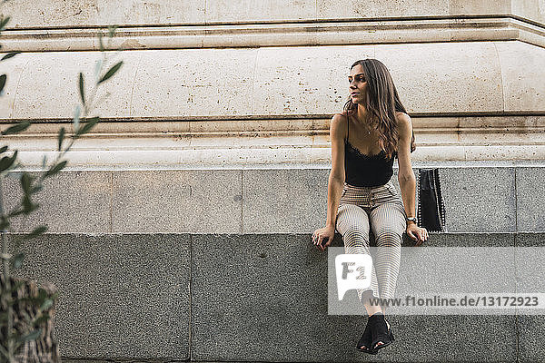 Young woman sitting on a wall waiting