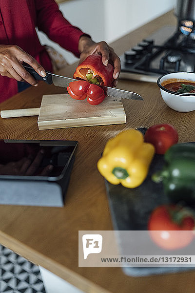 Hands of a woman  chopping bell peppers on a chopping board