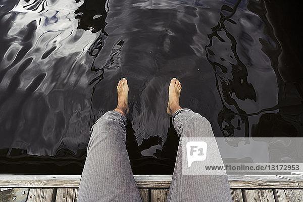 Mann sitzt auf einem Steg an einem See und baumelt mit den Füßen im Wasser