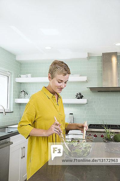 Lächelnde junge Frau bereitet in der Küche Salat zu