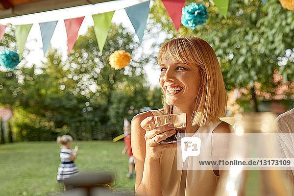 Glückliche Frau trinkt Kaffee auf einer Gartenparty Glückliche Frau trinkt Kaffee auf einer Gartenparty