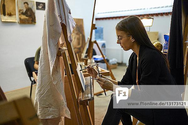 Schüler malen im Kunstunterricht an der Staffelei