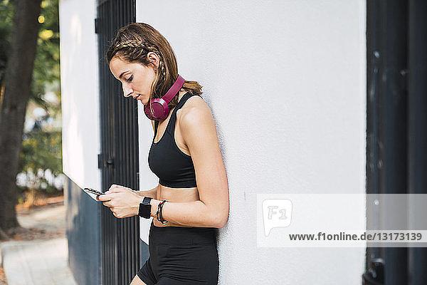 Fitte junge Frau  die nach dem Training ein Smartphone benutzt