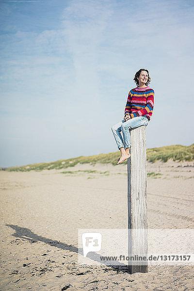 Reife Frau sitzt auf einem Holzpfahl am Strand