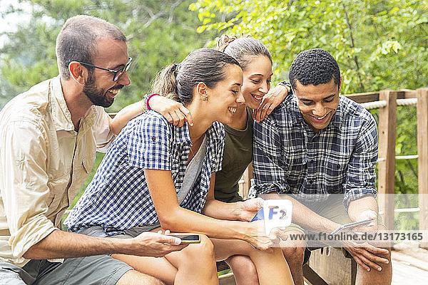 Italien  Massa  lächelnde Wanderer in den Alpi Apuane  die auf ihre Smartphones schauen und auf einer Bank sitzen