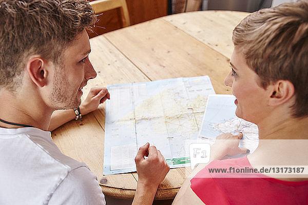 Junges Paar sitzt zu Hause am Tisch mit Karte