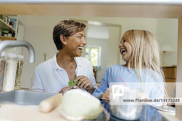 Lachende Mutter und Tochter spielen zu Hause mit der Spielzeugküche