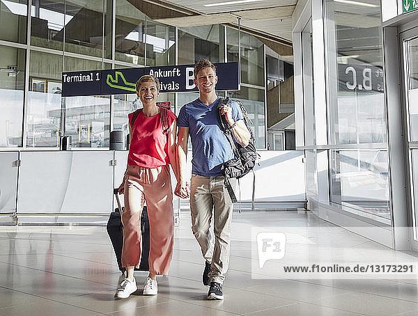 Glückliches Paar geht Hand in Hand auf dem Flughafen