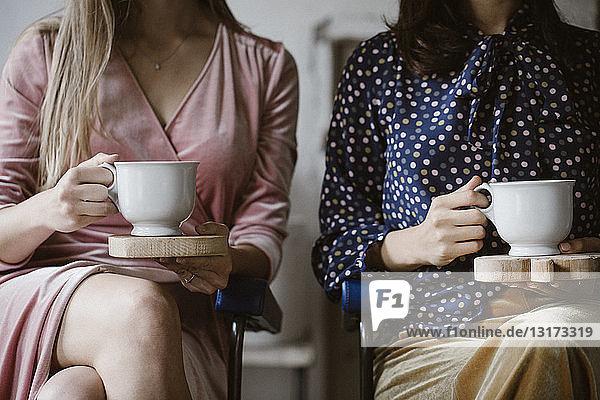 Zwei nebeneinander sitzende Frauen halten Holzbretter mit weißen Teetassen  Teilansicht