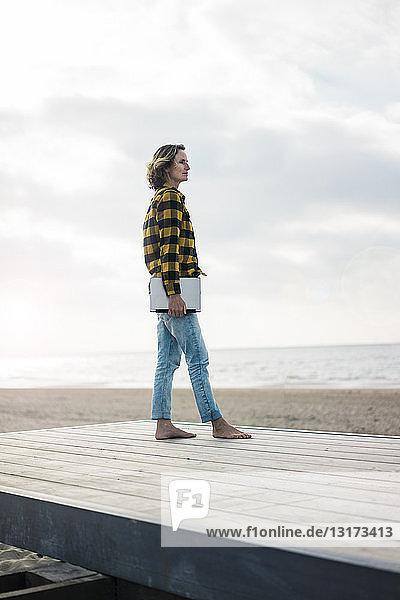 Eine reife Frau steht am Strand auf der Strandpromenade und hält einen Laptop