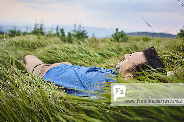 Relaxed man lying in grass